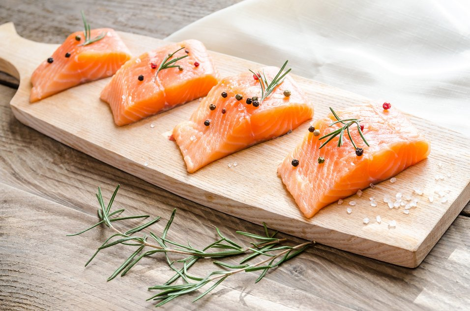 Salmon fillets on a wood platter with caper and salt garnish